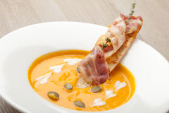 Pumpkin cream soup purée with bread slice, bacon and seeds Stock Photo