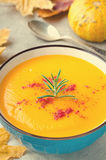 Pumpkin cream soup with rosemary and paprika in blue bowl. Halloween Thanksgiving Autumn food concept Royalty Free Stock Photo