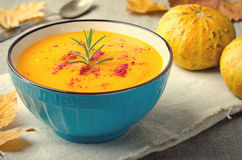 Pumpkin cream soup with rosemary and paprika in blue bowl. Halloween Thanksgiving Autumn food concept Royalty Free Stock Photography