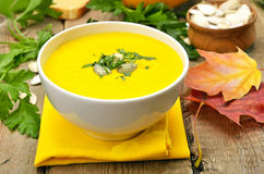 Pumpkin cream soup on wooden table Royalty Free Stock Images
