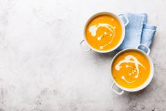Pumpkin creamy soup decorated with fresh cream stock image