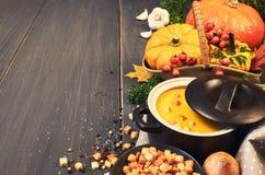 Pumpkin creme soup in ceramic pan on dark wood, space Royalty Free Stock Photography