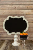 Pumpkin cupcake with blank chalkboard sign Royalty Free Stock Photos