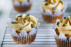 Pumpkin cupcake with buttercream and pumpkin seeds, close-up Royalty Free Stock Photos