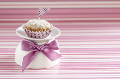 Pumpkin cupcake on white cup decoreted with satin silk bow Royalty Free Stock Photos