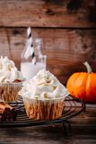 Pumpkin cupcakes decorated with cream cheese frosting. On wooden background Stock Image