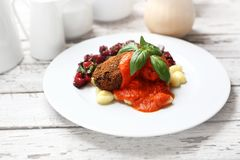 Pumpkin cutlets served with tomato sauce on dumplings on gnocchi, roasted beet salad stock photos