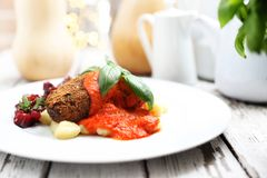 Pumpkin cutlets served with tomato sauce on dumplings on gnocchi, roasted beet salad stock image