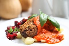 Pumpkin cutlets served with tomato sauce on dumplings on gnocchi, roasted beet salad stock images