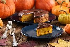 Pumpkin Dessert. Delicious Pumpkin Cake With Chocolate Icing Served With Small Bright Orange Pumpkins And Marple Leaves Royalty Free Stock Photography