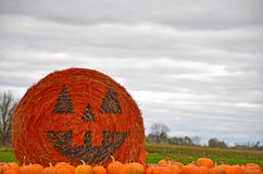Pumpkin face on hay bale Stock Image