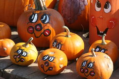 Pumpkin faces. Pumpkins painted with cheerful, colorful faces royalty free stock photo