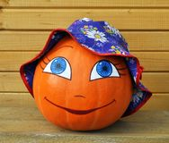 Pumpkin with female face in a children's hat Royalty Free Stock Image