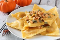 Pumpkin ravioli pasta, close up on a white plate Stock Photos