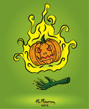 Pumpkin in fire floating on the devil hand on green background,h Royalty Free Stock Photo