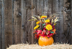 Pumpkin flower arrangement on hay Royalty Free Stock Photo