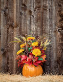 Pumpkin flower arrangement on hay. Against rustic wooden background Stock Photography