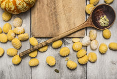 Pumpkin gnocchi with pumpkin,  wooden spoon,almonds , flour on wooden cutting board, on wooden rustic background top view Royalty Free Stock Photography