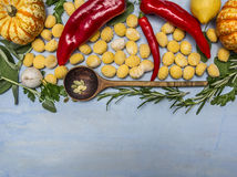 Pumpkin gnocchi with wooden spoon and autumn fruits vegetables and herbs on blue wooden background top view Royalty Free Stock Photos