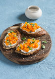 Pumpkin and goat`s cheese bruschetta on a wooden cutting board on blue background. Stock Images