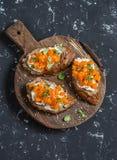 Pumpkin and goat's cheese bruschetta on a wooden cutting board on dark background. Stock Photo