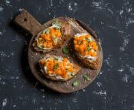 Pumpkin and goat's cheese bruschetta on a wooden cutting board on dark background. Stock Photos