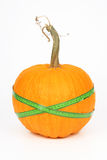 Pumpkin and green measured tape Royalty Free Stock Image