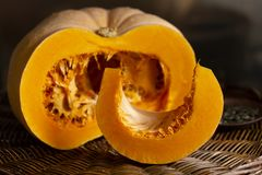 Pumpkin half and a slice with seeds on brown background. stock images