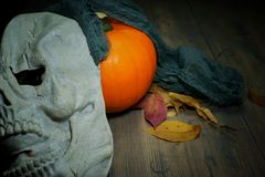 Pumpkin and halloween mask on old wood table stock image