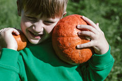 Pumpkin in the hands of 5 year-old boy in a green sweater Royalty Free Stock Photo