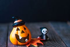 Pumpkin with a face and a skeleton in a hoodie. Pumpkin in a hat with a face and a skeleton in a hoodie royalty free stock image