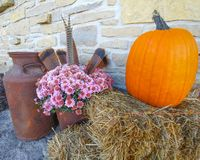 Pumpkin on Haystack with Purple Mums royalty free stock images