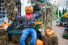 Pumpkin head. Scarecrow with a pumpkin head, sitting on a bench Royalty Free Stock Photo