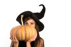 Pumpkin head jack lantern. Trick or treat. Woman posing with Pumpkin. Beautiful young surprised woman in witches hat and. Costume holding pumpkin stock photography