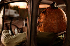 Pumpkin Head Man Sitting on a Old Rusty Truck Royalty Free Stock Photography