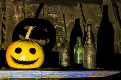 Pumpkin head and old bottles with scary shadows stock images