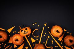 Pumpkin heads and confetti for Halloween party decor on black table top view. Flat lay style. stock photography