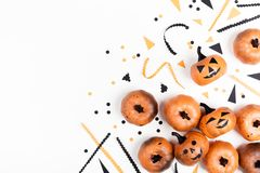 Pumpkin heads and confetti for Halloween party decor on white background top view. Flat lay style. stock photo