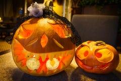 Pumpkin is holding a bitcoin in the teeth. Pumpkin is holding the bitcoin and ethereum coins in the teeth at Halloween Stock Image