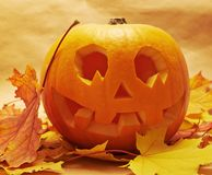 Pumpkin Jack-o'-lantern over maple-leaf Royalty Free Stock Images
