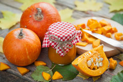Pumpkin jam, puree or sauce and ripe pumpkins on table Royalty Free Stock Photography