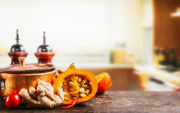 Pumpkin on kitchen desk table with cooking pot, oil and ginger at kitchen room background, front view. Autumn cooking inspiration Stock Photos