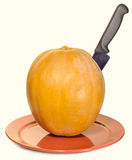 Pumpkin with a knife on a plate Royalty Free Stock Images