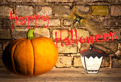 Pumpkin and lamp are located on the shelf, the bat hangs on a wall in a vault. Stock Photography