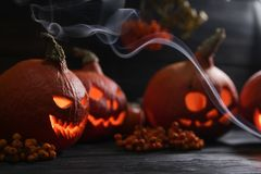 Pumpkin lantern lighting on a dark background. Several orange pumpkin lanterns with a scary faces for halloween holiday lighting on a dark background, with royalty free stock image