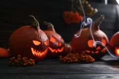 Pumpkin lanterns lighting on a dark wooden background. Several orange pumpkin lanterns with a scary faces for halloween holiday lighting on a dark background stock photo