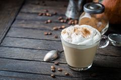 Pumpkin latte with whipped cream. And spices, with pumpkins over wood texture. Copy space royalty free stock photo