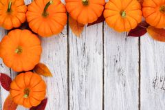 Pumpkin and leaves corner border over rustic white wood. Autumn leaves and pumpkin corner border over a rustic white wood background Royalty Free Stock Images