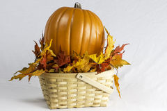Pumpkin and Leaves in a Wooden Basket Royalty Free Stock Images