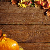 Pumpkin with leaves on a wooden cutting board Royalty Free Stock Photo